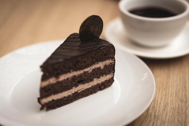 Un pezzo di deliziosa torta al cioccolato su un piatto bianco e una tazza di cioccolata calda Foto Premium