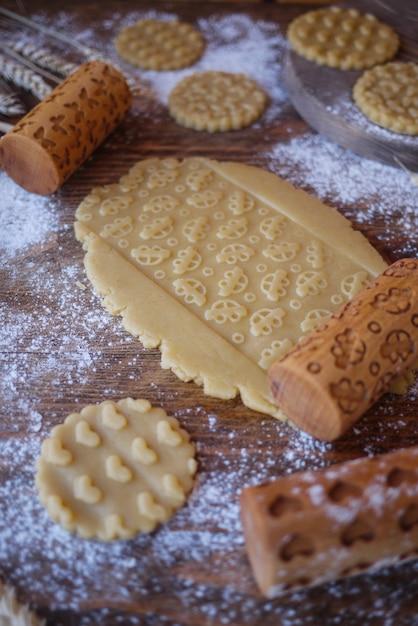 Un pezzo di pasta con una stampa di auto per bambini. mattarelle in legno per biscotti Foto Premium