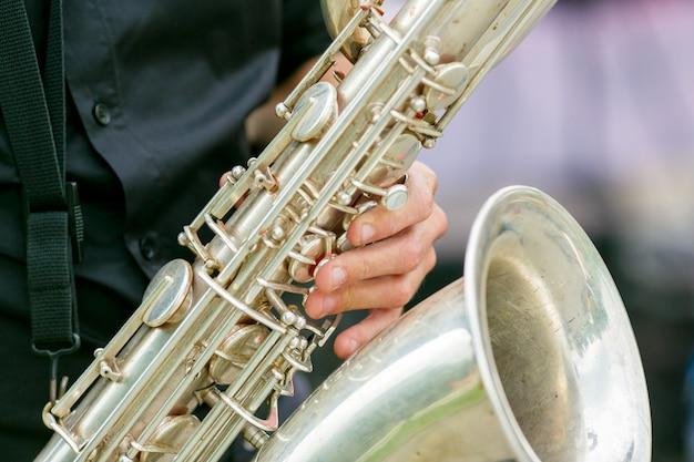 Un piano di primo piano del sassofono nelle mani del sassofonista Foto Premium