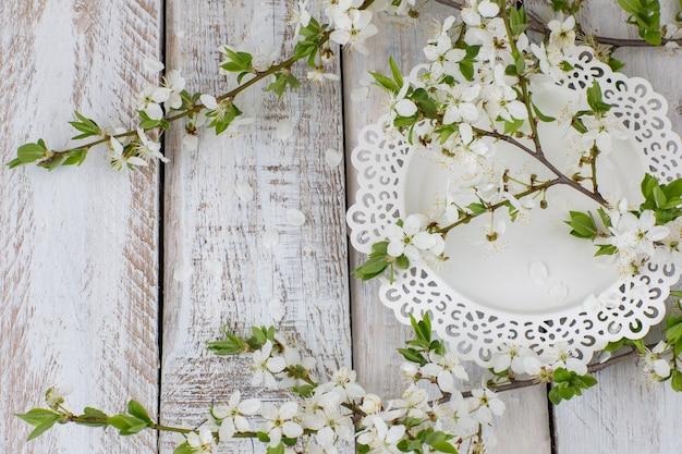 Un piatto bianco e un ramo di fiori di ciliegio Foto Premium