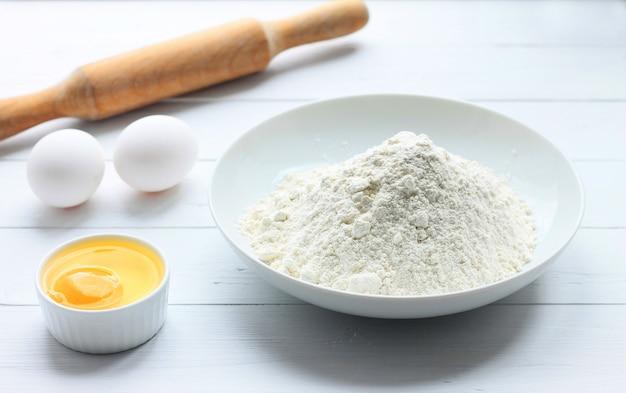 Un piatto con farina, uova, un mattarello su un fondo di legno bianco. Foto Premium