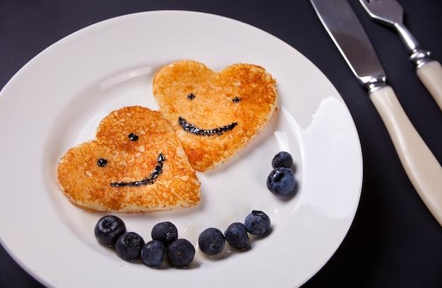 Un piatto di due pancake sotto forma del cuore con le bacche sulla tavola bianca Foto Premium