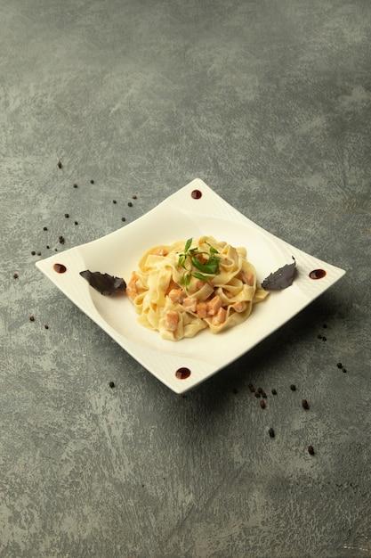 Un piatto di fettuccini con pollo in semplice sfondo grigio Foto Gratuite