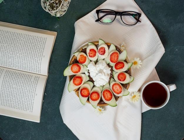 Un piatto di waffle con frutta e gelato e una tazza di tè. vista dall'alto. Foto Gratuite