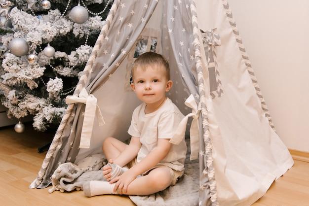 Un piccolo bambino carino è seduto nella stanza dei bambini in una tenda lodge wigwam accanto all'albero di neve di natale Foto Premium