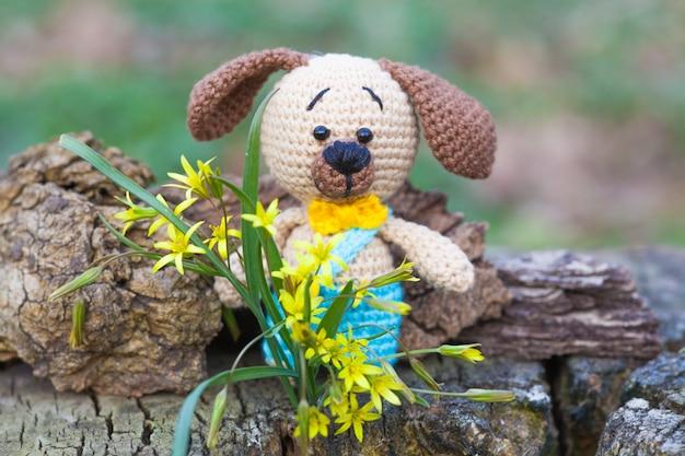 Un piccolo cane marrone in pantaloni blu. giocattolo lavorato a maglia, fatto a mano, amigurumi Foto Premium