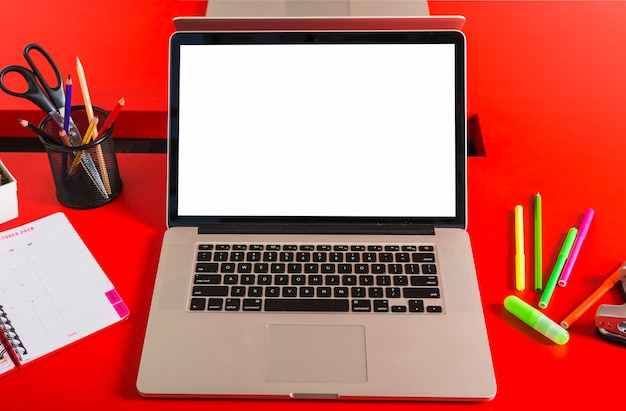 Un portatile con schermo vuoto con stationery sul tavolo rosso Foto Gratuite