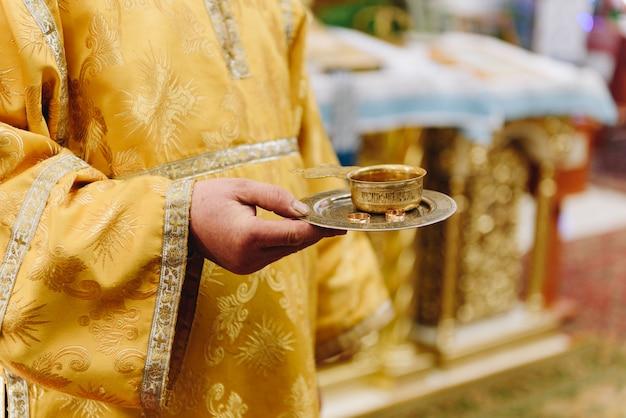 Un prete in chiesa con in mano un vassoio con fedi nuziali Foto Premium