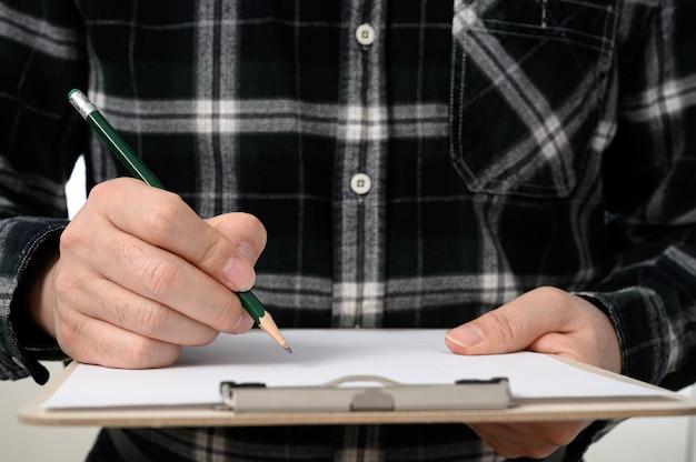 Un primo piano della mano di un uomo che firma un documento con una lavagna per appunti. Foto Premium