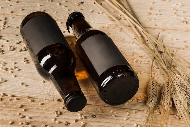 Un primo piano di due bottiglie da birra e spighe di grano su fondo di legno Foto Gratuite