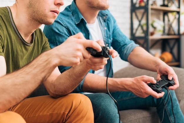 Un primo piano di due giovani che giocano una console per videogiochi a casa Foto Gratuite