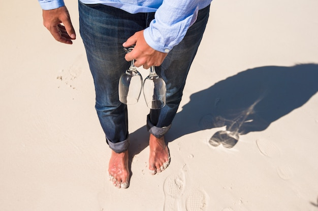Un primo piano di due vetri disponibili all'uomo che cammina a piedi nudi sulla spiaggia bianca Foto Premium