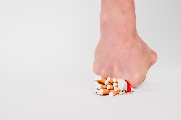 Un pugno di persona che schiaccia pacchetto di sigarette su sfondo bianco Foto Gratuite