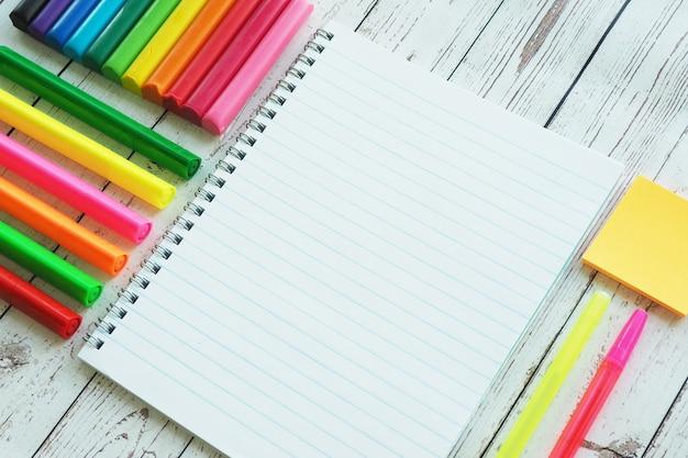 Un quaderno aperto, pennarelli colorati, penne e argilla Foto Premium