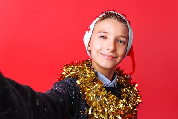 Un ragazzo adolescente fa un selfie con un cappello da babbo natale e orpelli sul collo Foto Premium