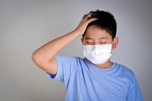 Un ragazzo asiatico indossa una maschera, coprendosi bocca e naso, prevenendo il coronavirus o covid-19. concetto di salute dei bambini Foto Premium