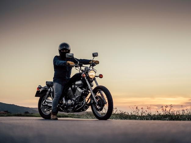 Un ragazzo aspetta con la moto sulla strada Foto Premium