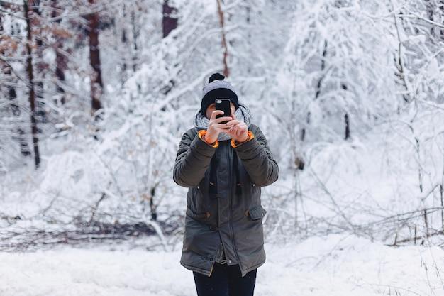 Un ragazzo che cammina lungo una strada innevata nei pressi di una pineta con il telefono Foto Premium