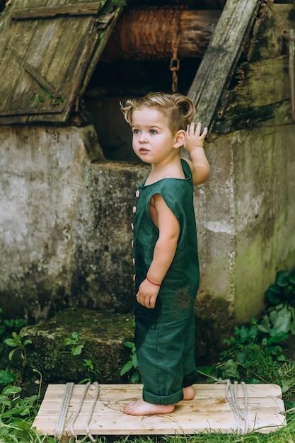 Un ragazzo con i capelli bianchi in una combinazione verde giocato a un pozzo Foto Premium