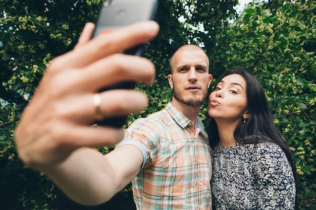 Un ragazzo con una ragazza che fa autoscatti su un fogliame verde. Foto Premium