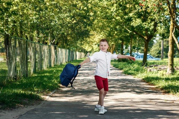 Un ragazzo di una scuola elementare con uno zaino per strada Foto Premium