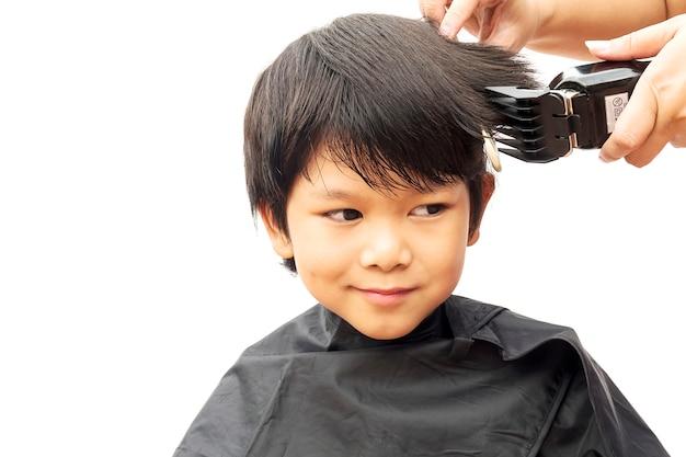 Un ragazzo è tagliato i capelli dal parrucchiere isolato su sfondo bianco Foto Gratuite