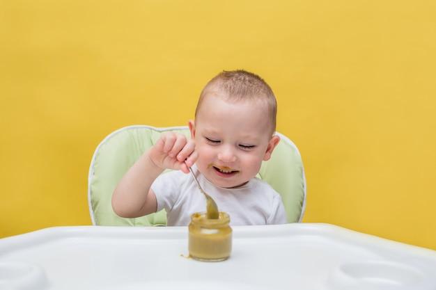 Un ragazzo felice mangia da soli alimenti per bambini a un tavolo su un giallo isolato Foto Premium