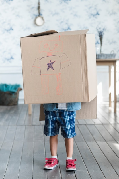 Un ragazzo in piedi con una scatola di cartone in testa con robot disegnato Foto Gratuite