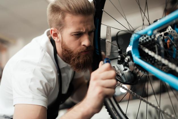 Un ragazzo ripara una bicicletta. indossa un grembiule. Foto Premium