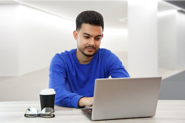 Un ragazzo seduto a un laptop in cerca di lavoro su internet, che fa affari nella rete globale con una tazza di caffè. sulla luce Foto Premium