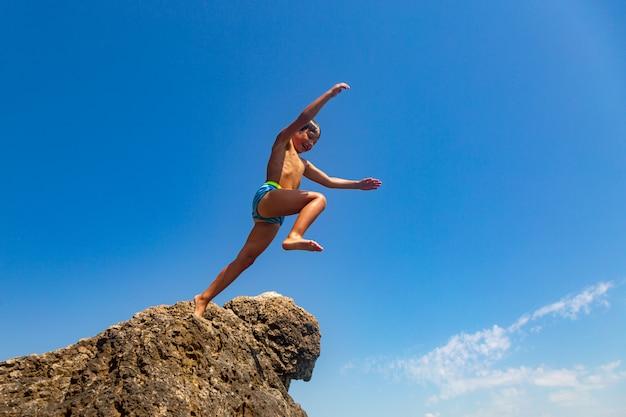Un ragazzo sta saltando dalla scogliera verso il mare in una calda giornata estiva. vacanze al mare. turismo attivo e ricreazione Foto Premium
