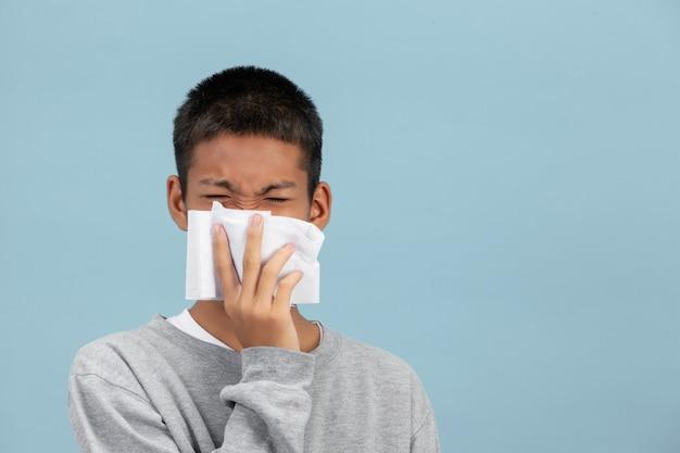 Un ragazzo starnutisce nei tessuti e si sente male sulla parete blu. Foto Gratuite