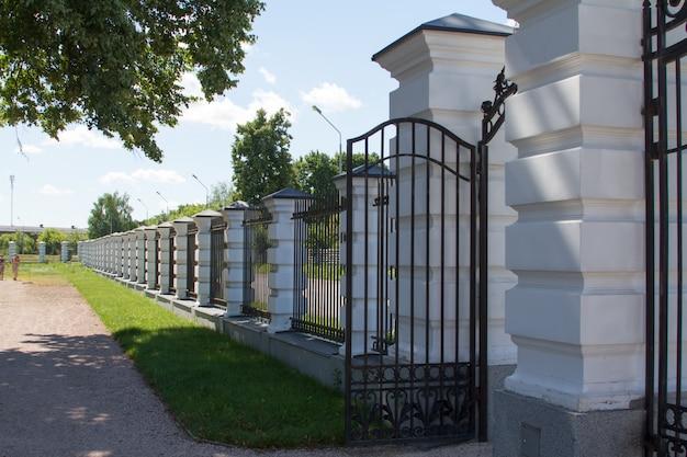 Un recinto con colonne e una grata vicino alla strada asfaltata e parco inglese Foto Premium