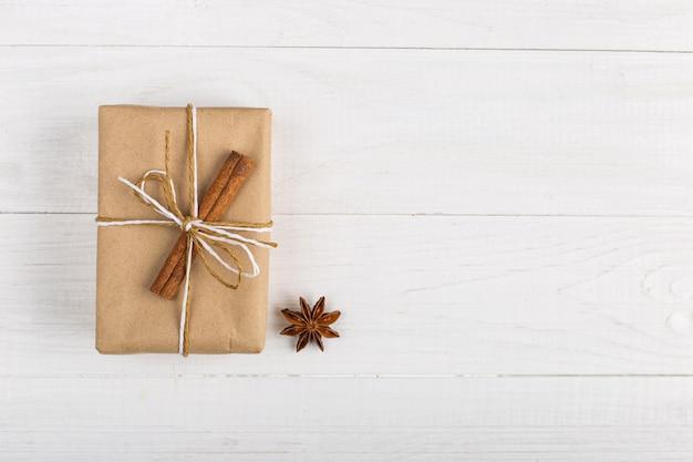 Un regalo di carta artigianale con cannella e anice stellato su un tavolo bianco. Foto Premium