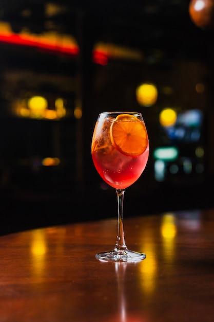 Un rinfrescante cocktail freddo con fette di ghiaccio e arancia in un bicchiere di vino Foto Premium