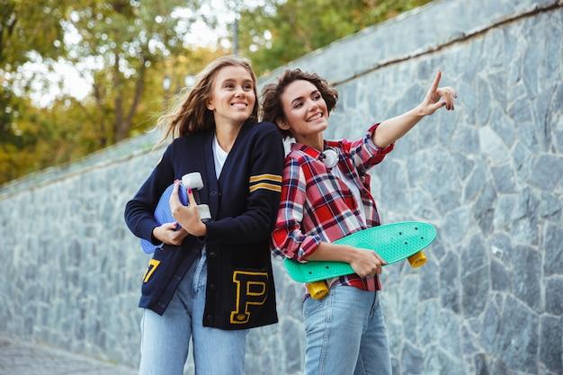 Un ritratto di due adolescenti allegri che tengono i pattini Foto Gratuite