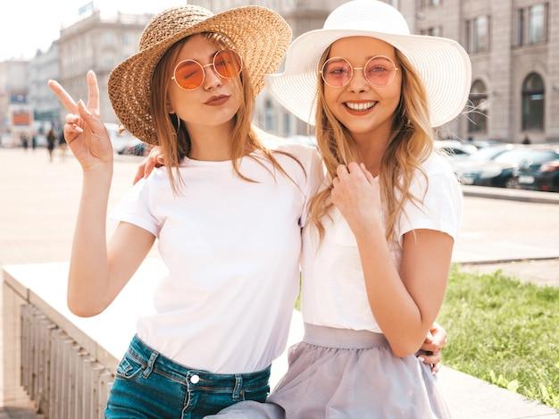 Un ritratto di due giovani belle ragazze sorridenti bionde dei pantaloni a vita bassa in vestiti bianchi della maglietta dell'estate d'avanguardia. Foto Gratuite