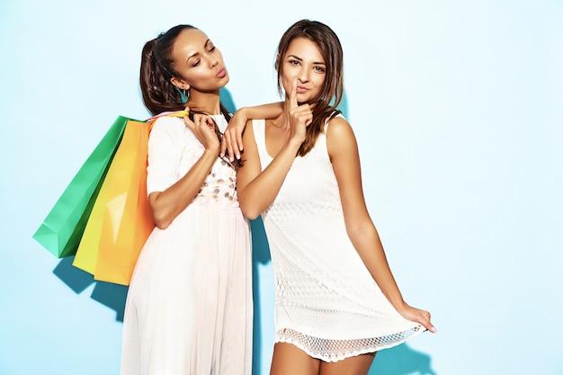 Un ritratto di due giovani donne castane sorridenti alla moda sexy che tengono i sacchetti della spesa. donne calde vestite in abiti hipster estate. modelli positivi che posano sopra la parete blu Foto Gratuite