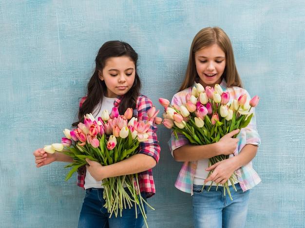 Un ritratto di due ragazze che stanno davanti al mazzo blu del fiore del tulipano della tenuta della parete Foto Gratuite