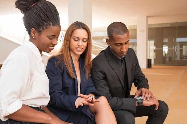 Un ritratto di tre persone di affari sorridenti che aspettano riunione Foto Gratuite