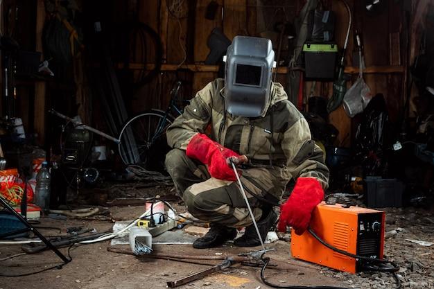 Un saldatore maschio in una maschera per saldatura lavora con un elettrodo ad arco nel suo garage. saldatura, costruzione, lavorazione dei metalli. Foto Premium