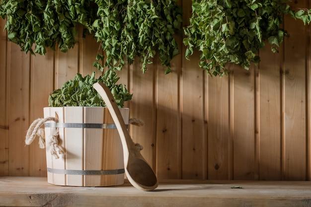 Un secchio di legno e una scopa di betulla in un bagno russo. sauna. Foto Premium