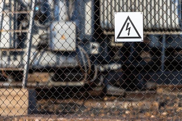 Un segnale di avvertimento dei pericoli dell'alta tensione elettrica è appeso al recinto della rete che circonda la sottostazione della linea elettrica. Foto Premium