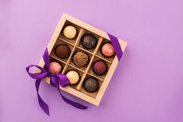 Un set di cioccolatini assortiti in una scatola di carta con un nastro di raso viola Foto Premium