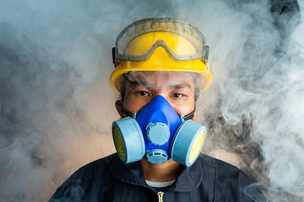 Un soccorritore indossa un respiratore in un'atmosfera tossica fumosa Foto Premium