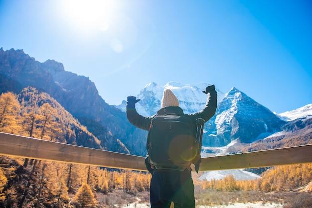 Un successo dell'uomo che fa un'escursione nella montagna di punta della neve all'autunno, concetto di viaggio della gente Foto Premium