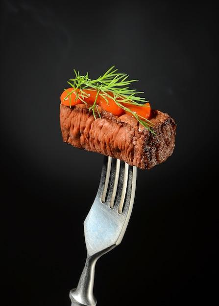 Un succoso pezzo di carne con ketchup e aneto viene piantato su una forchetta e. Foto Premium