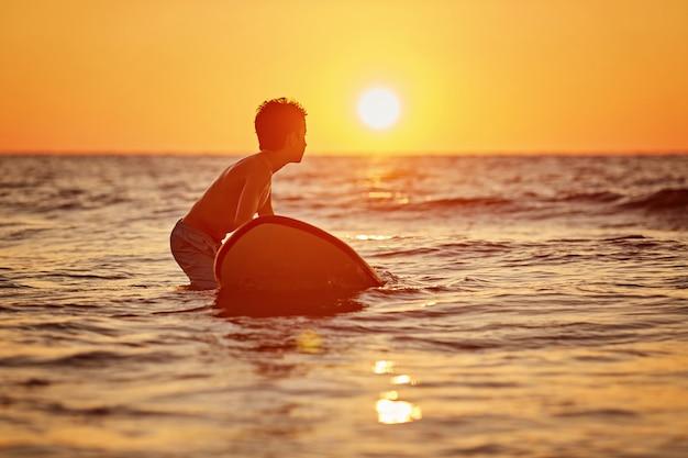 Un surfista con la sua tavola da surf in spiaggia Foto Premium