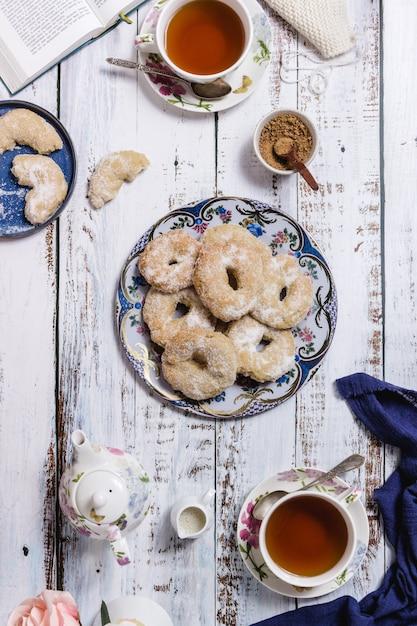 Un tavolo di legno bianco con due tazze di tè e dei pasticcini Foto Premium