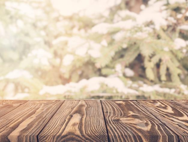 Un tavolo di legno vuota con alberi sfocati Foto Gratuite